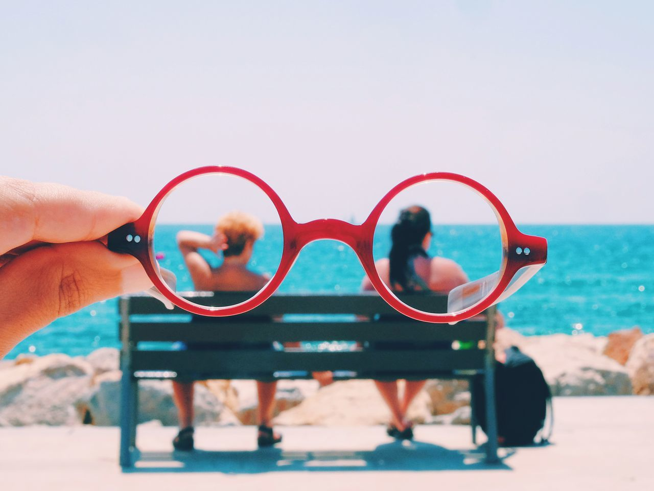 Couple sitting on bench on beach seen through eyeglasses