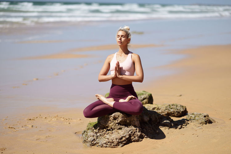 Woman mediating while sitting on rock at beach