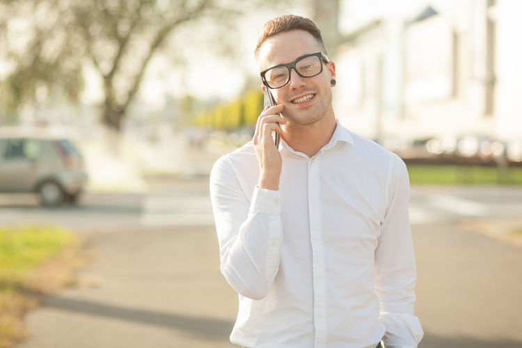 Portrait of smiling young man talking on mobile phone while standing in city