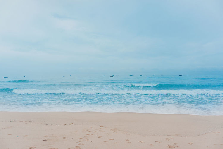 Soft Wave Of Blue Ocean On Clean Sandy Beach with Footprints Dog on Beach in Rayong, Thailand Beach Beauty In Nature Cloud - Sky Day Horizon Horizon Over Water Idyllic Land Nature No People Non-urban Scene Outdoors Sand Scenics - Nature Sea Sky Tranquil Scene Tranquility Turquoise Colored Water