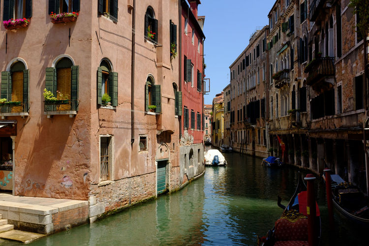 Boats moored in grand canal amidst old buildings