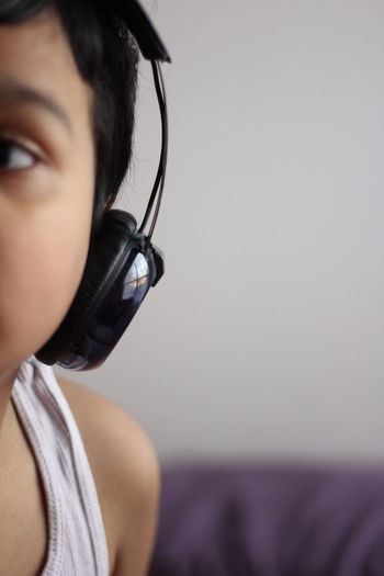 Cropped image of boy listening to music at home