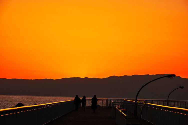 Rear view of silhouette people standing on mountain and sea  against orange sky at sunset