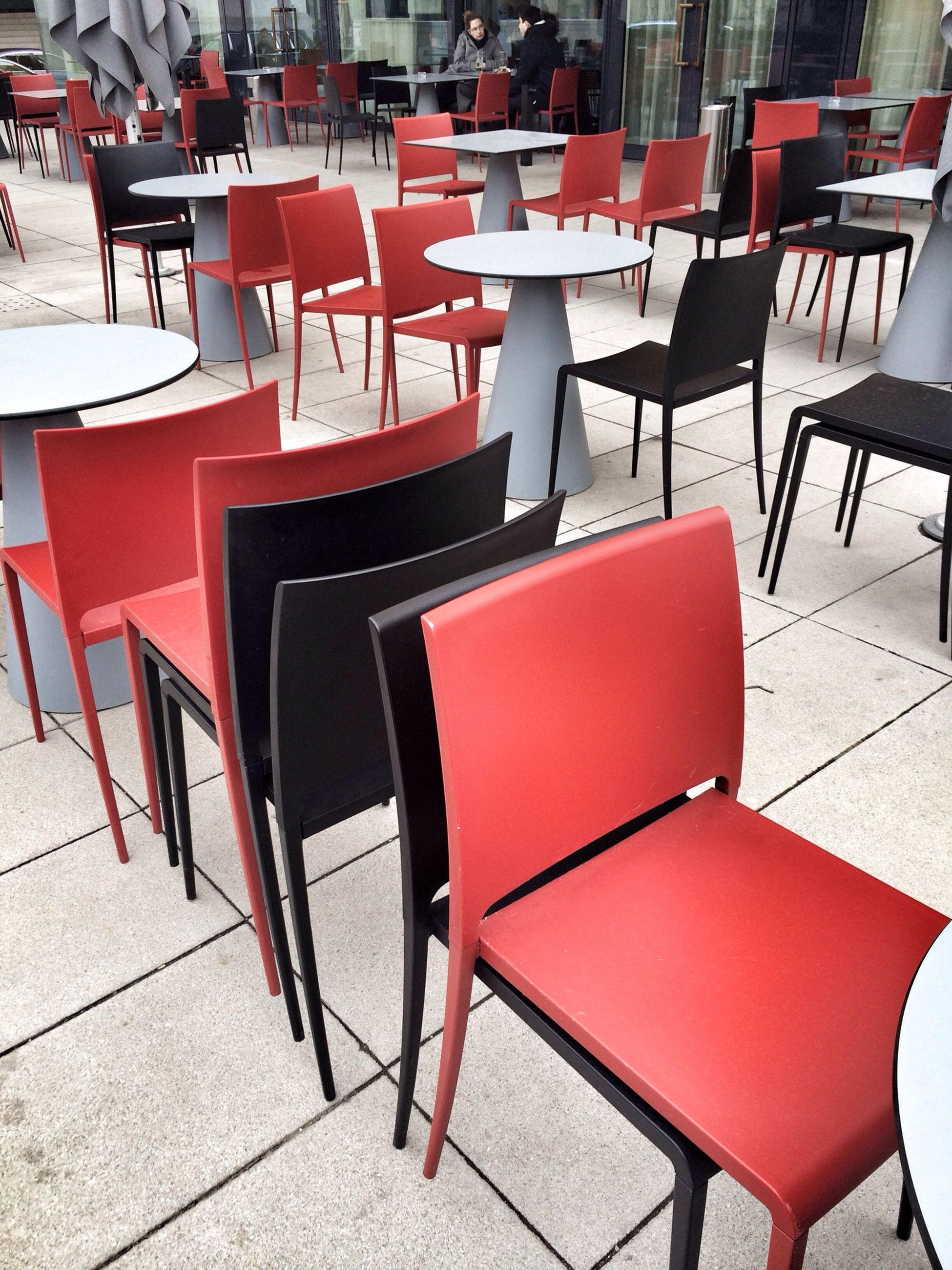 chair, empty, table, absence, seat, indoors, furniture, high angle view, tiled floor, arrangement, restaurant, in a row, sidewalk cafe, sunlight, shadow, red, built structure, flooring, no people, pattern