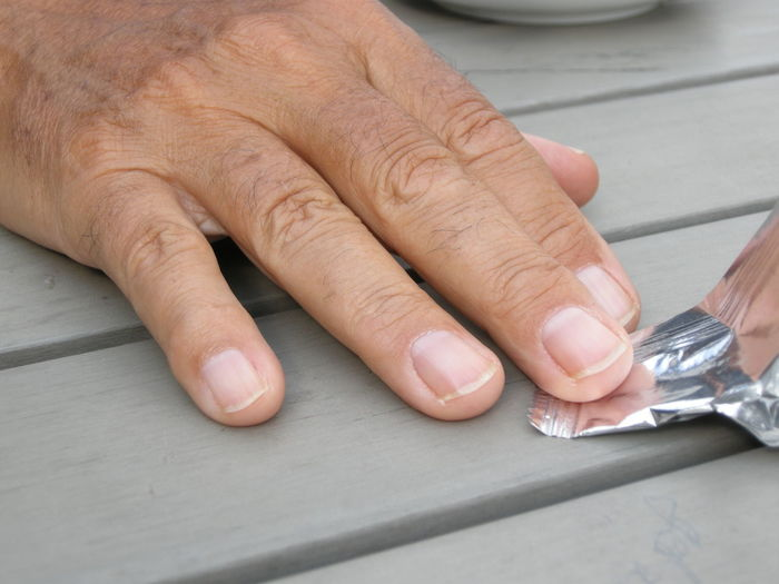 Cropped Hand Of Man Holding Candy Wrapper On Wooden Table