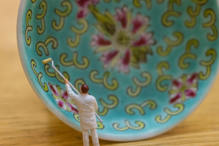 Close-Up Of Figurine Painting Bowl On Table