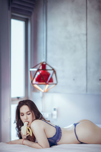 Sensuous Woman In Lingerie Eating Banana While Lying On Bed At Home