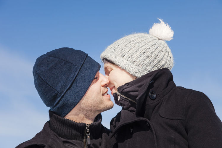 Low angle view of romantic couple kissing against sky during winter