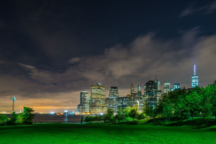 Grassy field against illuminated buildings and sky in park at night