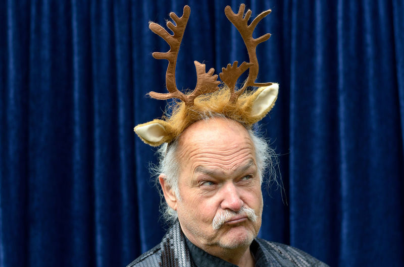 Close-Up Of Senior Entertainer Wearing Antlers At Event