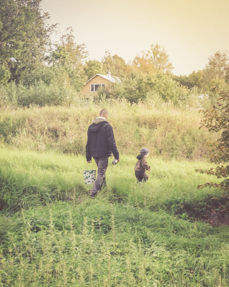 Father and son Natural Rural Casual Clothing Child Day Family Lifestyles Men Nature Outdoors People Plant Real People Rear View Retro Styled Rural Scene Two People Women