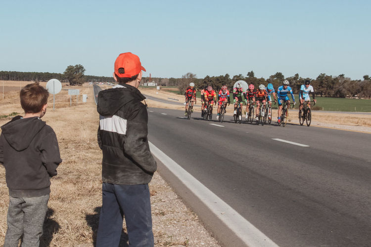 Side View Of Boys Looking At Cyclists Riding Bicycles On Road Against Clear Sky
