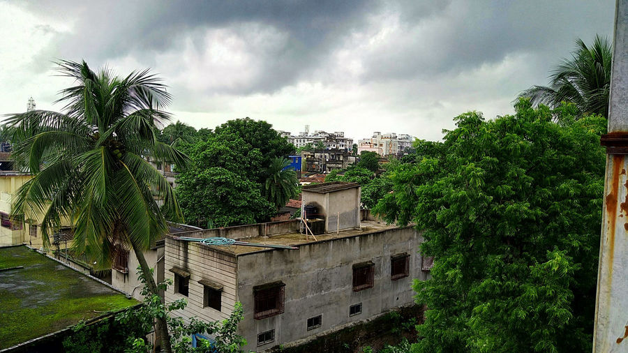 View of house and trees against cloudy sky