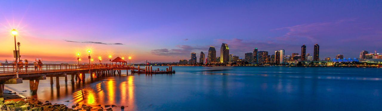 Panorama of Coronado old pier reflecting on in San Diego Bay from Coronado Island, California, USA. San Diego cityscape skyline with Downtown and Waterfront Marina District at twilight on background. Coronado Coronado Beach Coronado Island Sea Beach San Diego California United States America American Skyline Seascape Cityscape Sun Dock Port Holiday Vacations Sunset Night Panorama View Panorama Foto Pier City Architecture Water Building Exterior Built Structure Sky Urban Skyline Illuminated Travel Destinations City Life Building Landscape Reflection Office Building Exterior Transportation Nature Skyscraper Harbor Panoramic Bridge - Man Made Structure No People Outdoors Modern