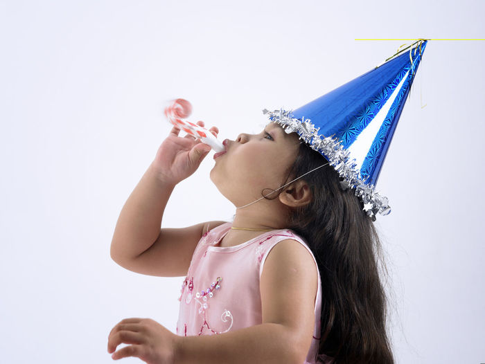 Girl blowing whistle against white background