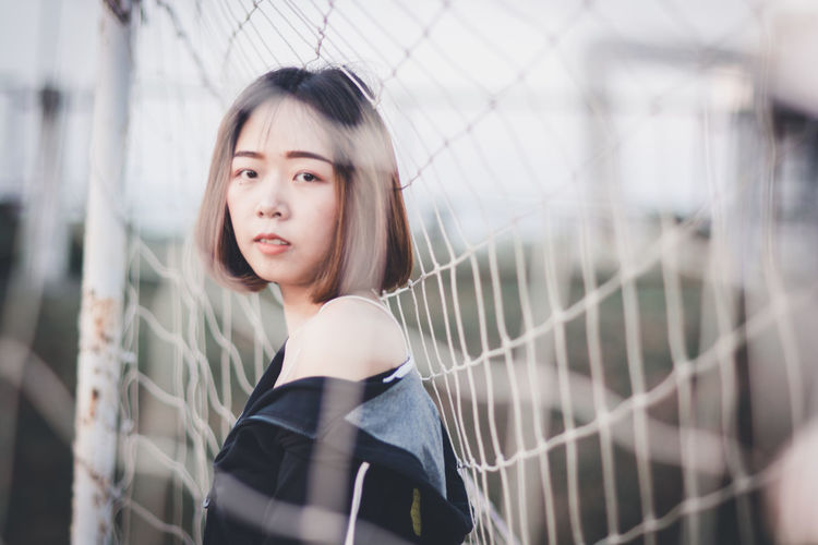 One Person Fence Portrait Looking Child Headshot Looking Away Selective Focus Childhood Barrier Boundary Real People Standing Casual Clothing Women Day Young Adult Contemplation Innocence Hairstyle Beautiful Woman Bangs Netherlands