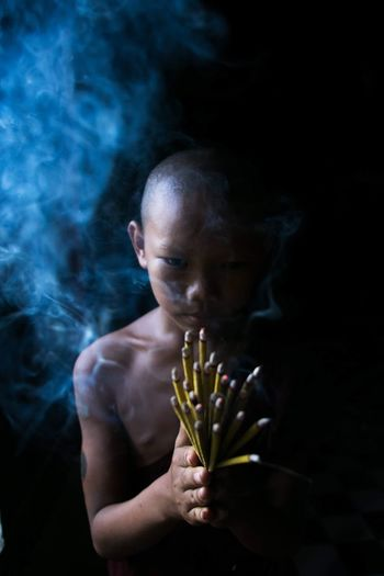 Portrait of shirtless boy holding incense while standing against black background