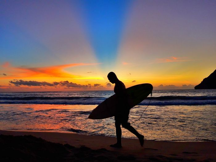 Full length of man with surfboard walking on shore at beach during sunset