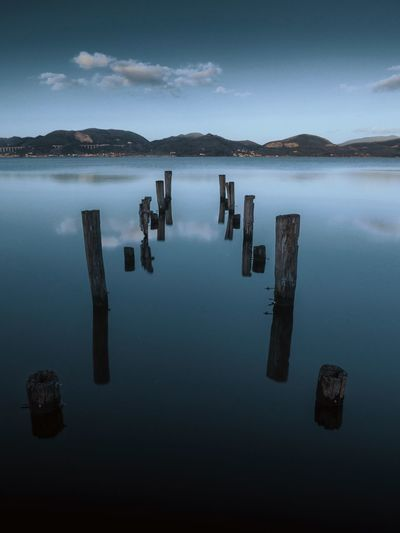High angle view of wooden posts in lake against sky