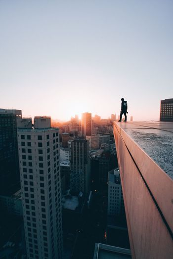 Man standing by modern buildings against sky during sunset