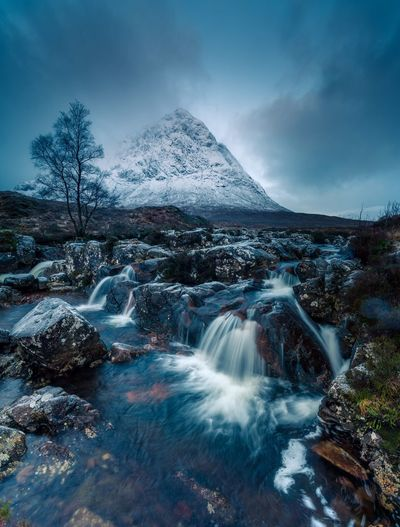 Scenic view of waterfall against snow and sky