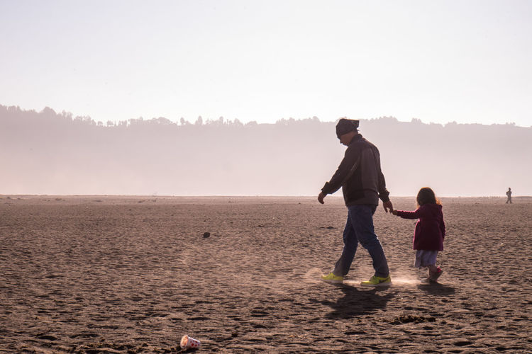Mother and daughter on beach against sky