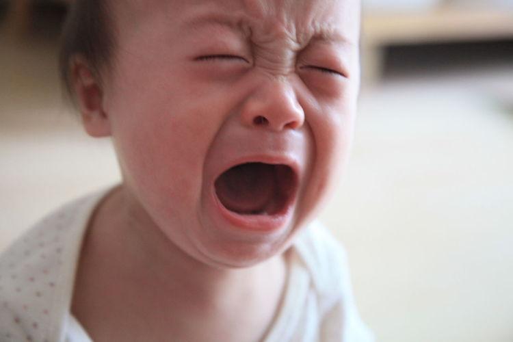 Cute boy crying at home