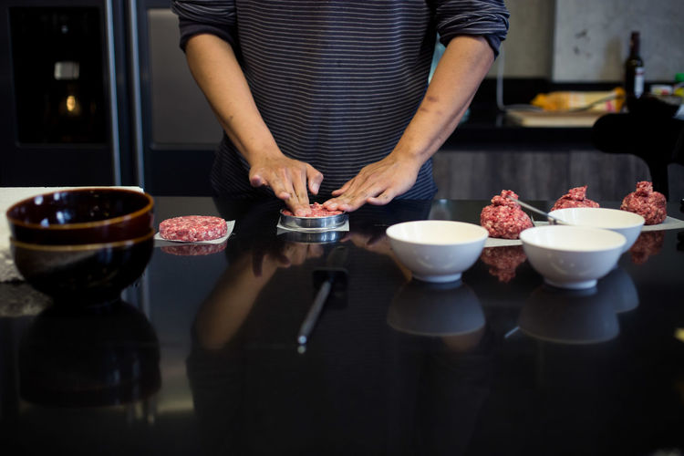 Midsection Of Man Shaping Meat At Kitchen