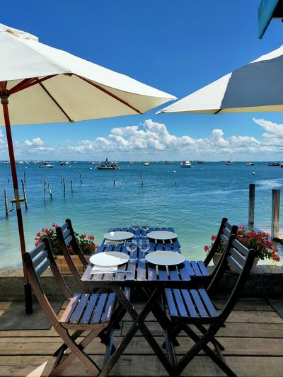 Chairs and tables at restaurant by sea against blue sky