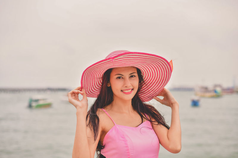 Beach Beautiful Woman Clothing Front View Hair Hairstyle Hat Holiday Horizon Over Water Land Leisure Activity One Person Outdoors Pink Color Portrait Sea Sky Sun Hat Trip Vacations Water Women Young Adult Young Women