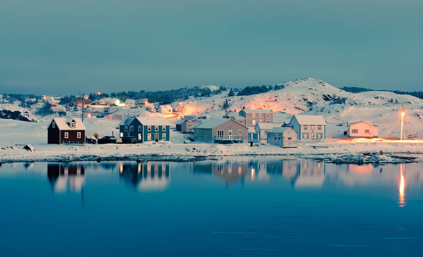 Calm winter evening in Durrell Harbor neighborhood of outport town of Twillingate, Newfoundland, NL, Canada Building Exterior Durrell Durrell Harbour Twillingate NL Newfoundland Newfoundland, Canada Canada Dusk Outport Winter Snow Evening Townscape, Travel Destinations Destination Architecture Built Structure Building Reflection Water Waterfront House No People Residential District Blue Outdoors