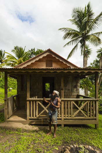 Man with Machete in front of an Antique House, Tet Paul Nature Trail, Saint Lucia Architecture Built Structure Day Front View Full Length Lifestyles One Person Outdoors Palm Tree People Real People Sky Standing Tree Young Adult