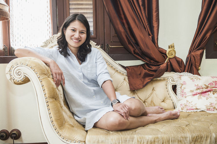 Full length portrait of smiling beautiful woman resting on chaise longue at home