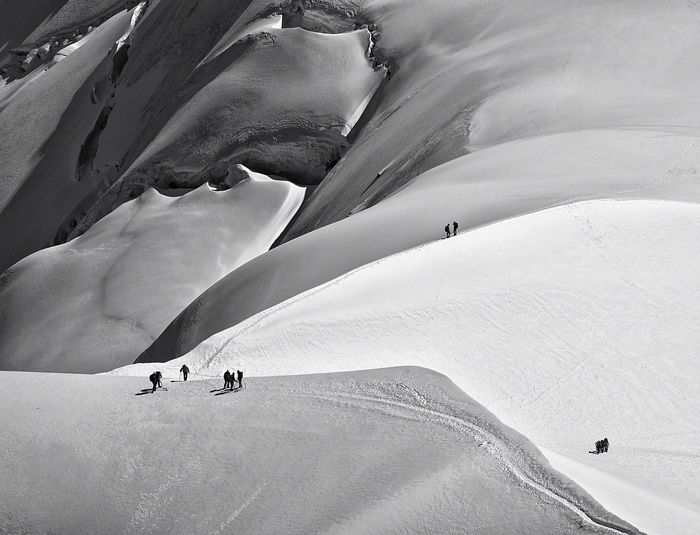 Aerial View Of Silhouette Hikers On Snowcapped Mountain