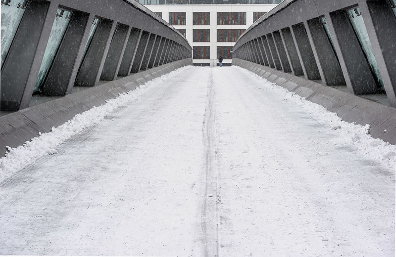 Empty road amidst buildings in city during winter