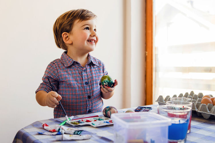 Smiling boy painting egg at home