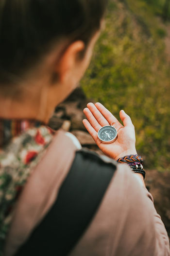 Midsection of woman holding compass outdoors