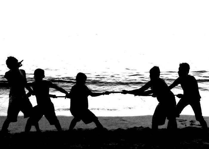 Silhouette people playing tug-of-war on beach