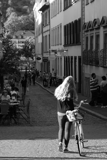 Rear view of women walking on bicycle in city
