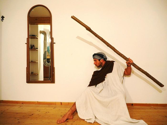 Man holding stick against wall