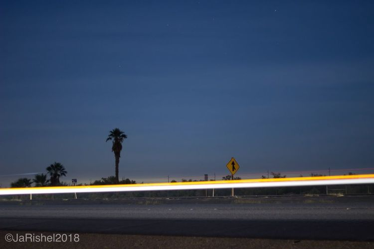 Road by sea against sky at night