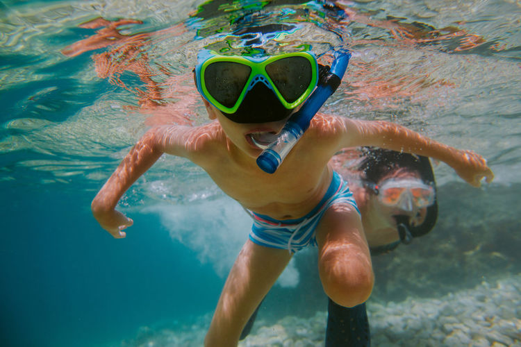 Child learning to snorkel with his mother in sea. Young boy wearing diving mask swimming under water. Snorkeling Snorkel Snorkelling Underwater Dive Sea Mast UnderSea Leisure Activity Sport Ocean Summer Holiday Vacation Outdoors Diver Swimming Goggles Gear Face Equipment Recreation  Exploring Boy Child