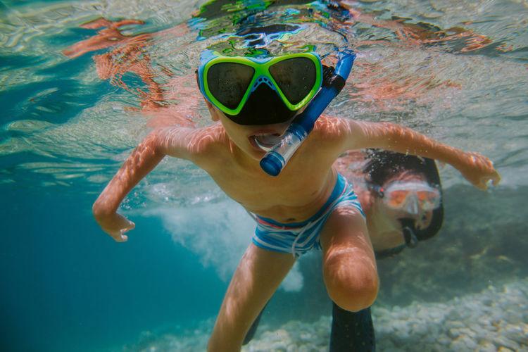Shirtless boy snorkeling in sea