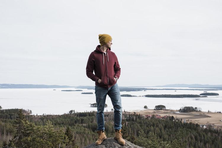 Full length of man standing on shore against sky