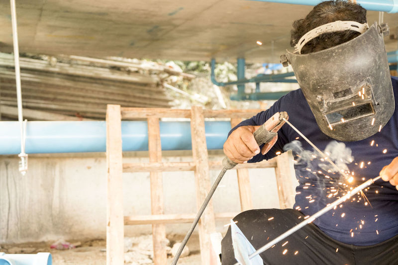 Welders Welding steel for construction. ,Work in the construction area Construction Craftsman Industry Light Skill  Smoke Welding Work Worker Workplace Labor Manufacture Manufacturing Mask Matal Protection Repair Safety Skilled Spark Steel Structure Tool Weld Welder