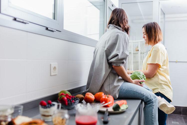 Cheerful women preparing food in kitchen