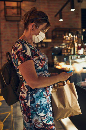 Mature woman wearing mask using mobile phone standing in cafe