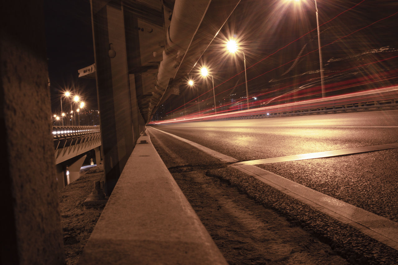 transportation, night, illuminated, street, street light, light trail, lighting equipment, architecture, road, city, light beam, long exposure, no people, motion, the way forward, direction, built structure, rail transportation, speed, mode of transportation, lens flare, outdoors, surface level