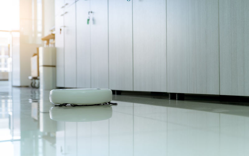 Robot vacuum cleaner cleaning floor in office. white robot vacuum cleaner for the smart home.