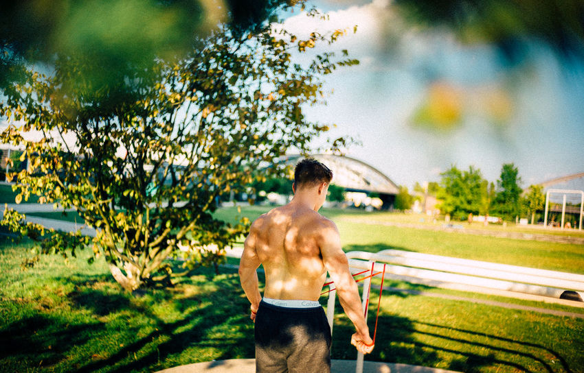 Adult Day Healthy Lifestyle Leisure Activity Lifestyles Men Muscular Build Nature One Person Outdoors Plant Real People Rear View Semi-dress Shirtless Shorts Standing Strength Tree Young Adult Young Men